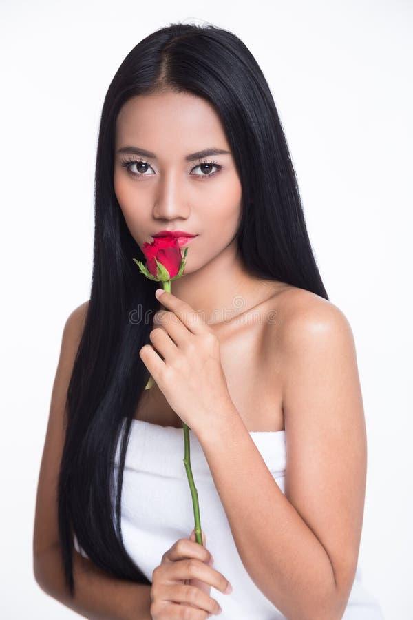 Señora hermosa asiática del retrato con la rosa del rojo en el fondo blanco foto de archivo libre de regalías