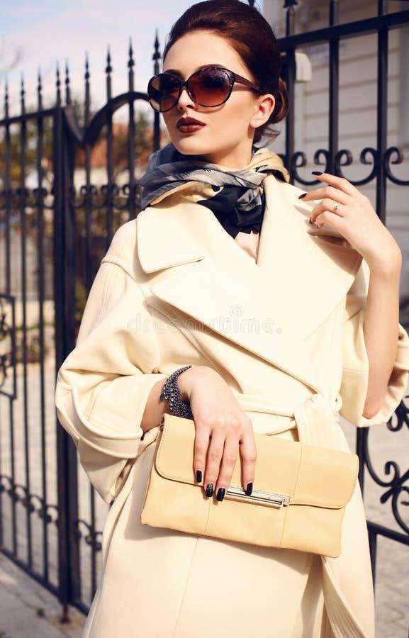 Señora hermosa con el pelo oscuro que lleva la capa y las gafas de sol elegantes fotos de archivo libres de regalías