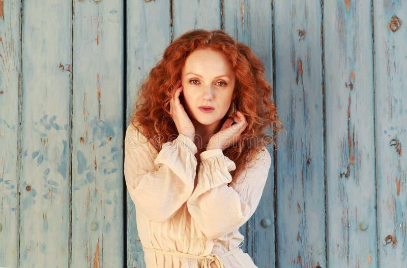 Señora hermosa con el pelo rojo ondulado largo, ahuecado principal en manos imagen de archivo libre de regalías