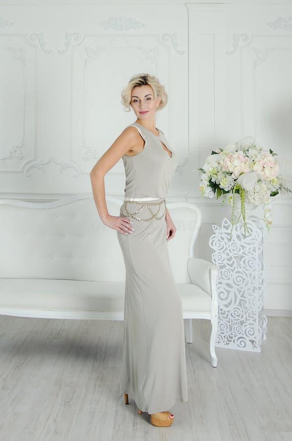 Señora hermosa de 40 años en un vestido de noche largo Interior elegante en color claro foto de archivo
