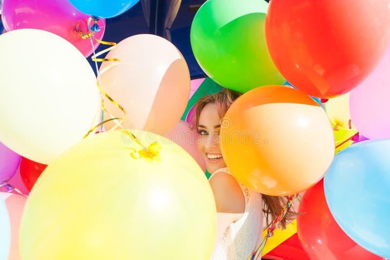 Señora hermosa en el equipo retro que sostiene un manojo de globos en el th imagenes de archivo