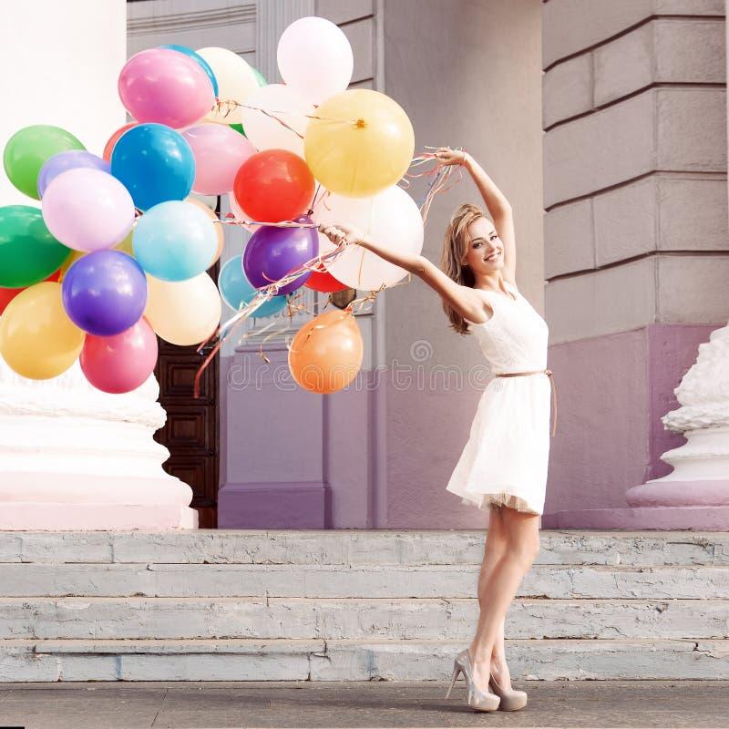 Señora hermosa en el equipo retro que sostiene un manojo de globos en el th fotografía de archivo