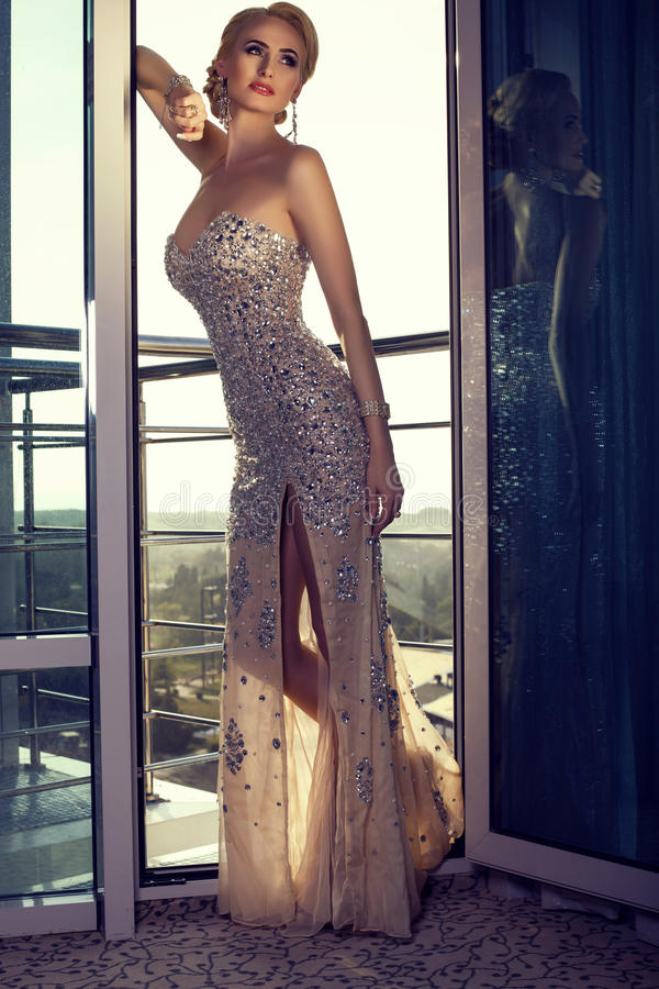 señora hermosa en el vestido elegante que presenta en el balcón imagen de archivo libre de regalías