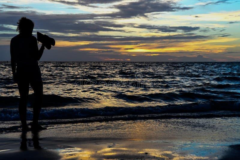 Señora hermosa en la puesta del sol imagen de archivo