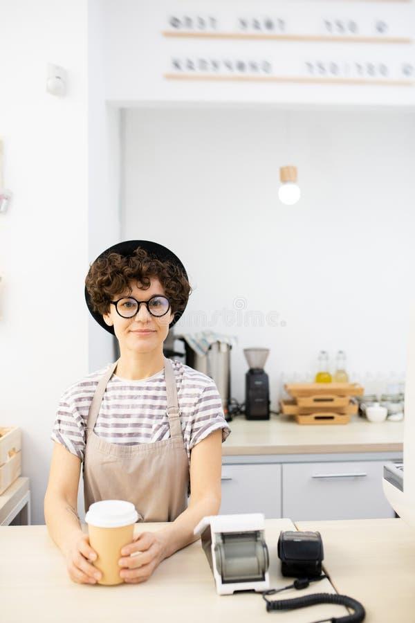 Señora hermosa en la situación del sombrero en el contador en café imágenes de archivo libres de regalías