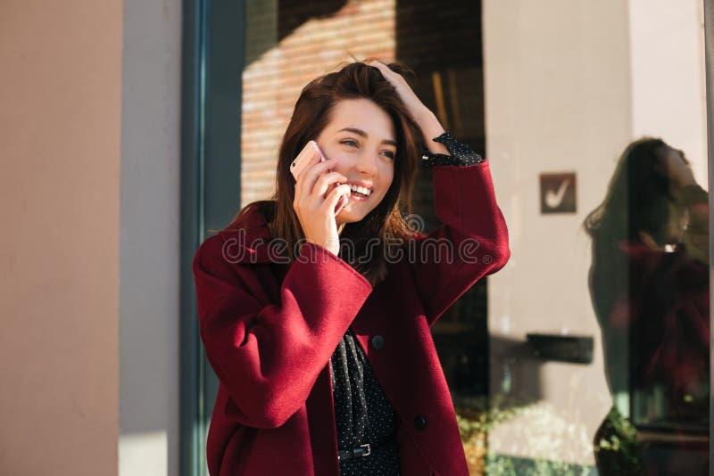 Señora hermosa joven en la situación de la capa en la calle que mira feliz a un lado mientras que habla en su teléfono móvil imagenes de archivo