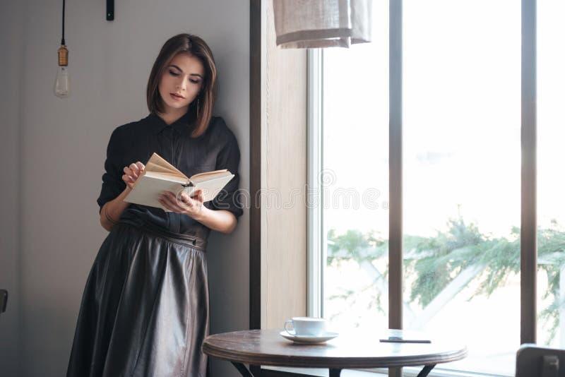 Señora hermosa joven que coloca la ventana cercana en café foto de archivo libre de regalías