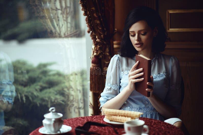 Señora hermosa joven que se sienta en la tabla en el café acogedor agradable con el libro en sus manos foto de archivo libre de regalías