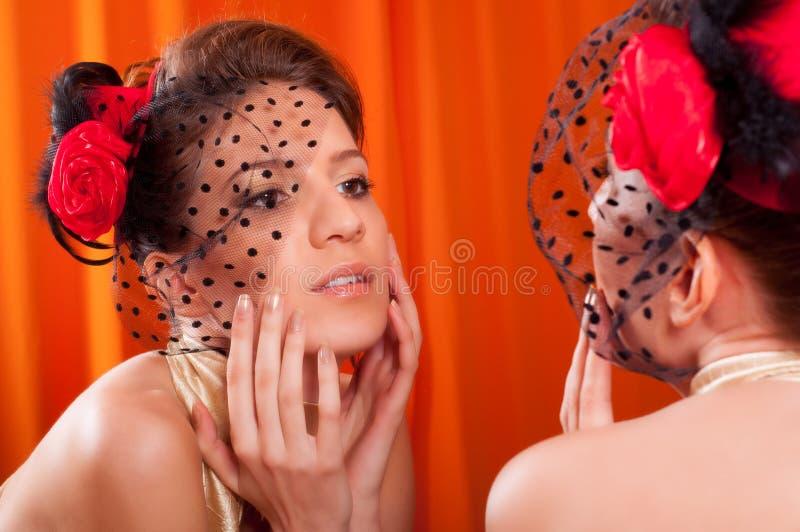 Señora hermosa que admira su cara en espejo fotos de archivo