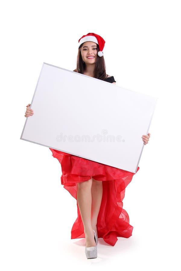 Señora hermosa que lleva a cabo al tablero vacío para el copyspace de la Navidad imagen de archivo