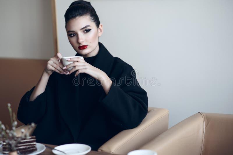Señora hermosa que se sienta en el café de consumición del café agradable y que come la torta fotos de archivo