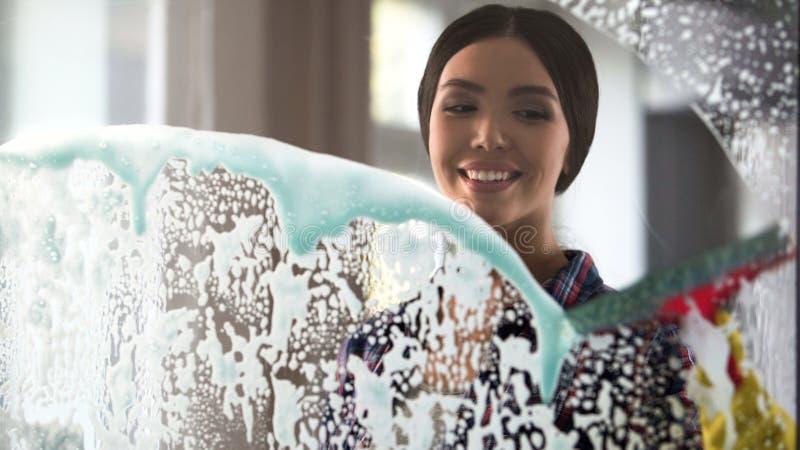 Señora joven activa que goza limpiando la casa, limpiando la superficie de cristal en sitio foto de archivo