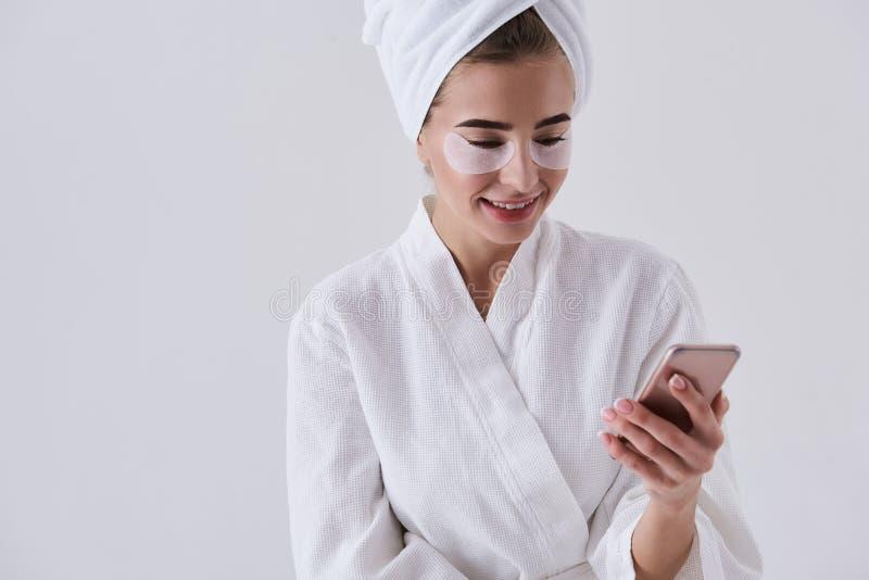 Señora joven alegre con los remiendos debajo de ojos usando el teléfono móvil fotografía de archivo libre de regalías