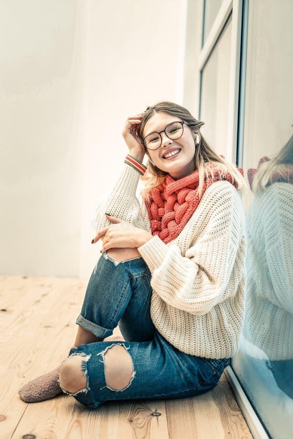 Señora joven alegre que se sienta en piso de madera cerca de la ventana imagenes de archivo