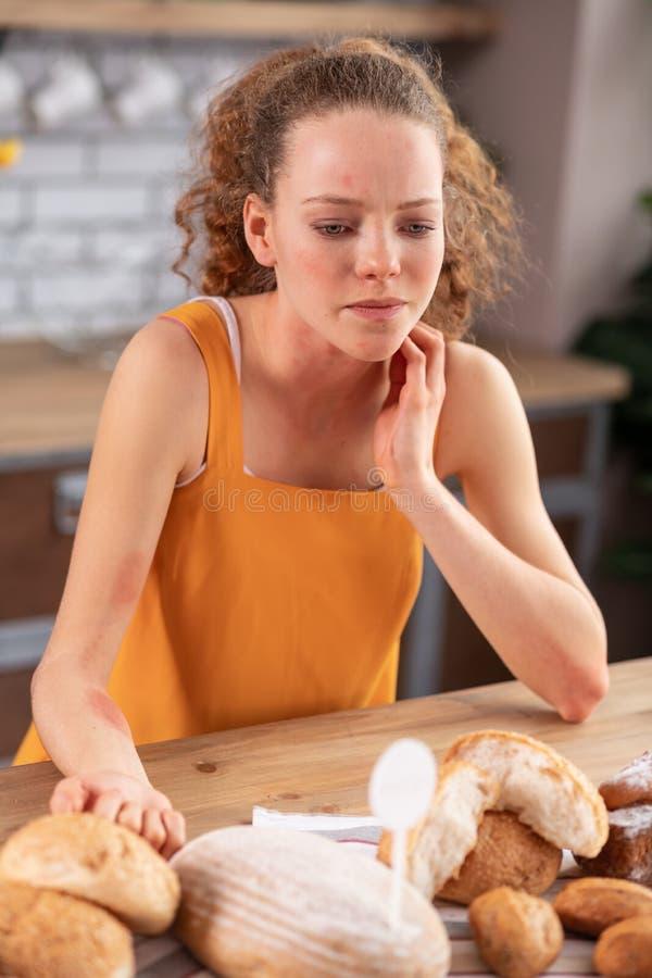 Señora joven apuesta desagradable que se inclina en la tabla de cocina y que frota su cuello fotos de archivo libres de regalías
