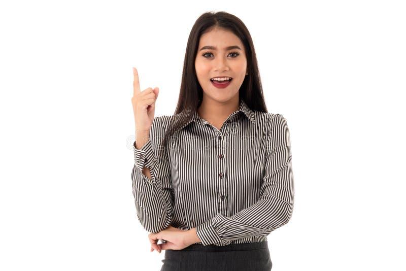 Señora joven asiática sonriente con el finger que señala encima de aislado en el fondo blanco imagenes de archivo