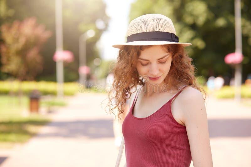 Señora joven atractiva dulce que se coloca en el centro del parque, mirando a un lado, disfrutando de tiempo en aire fresco, ropa foto de archivo libre de regalías