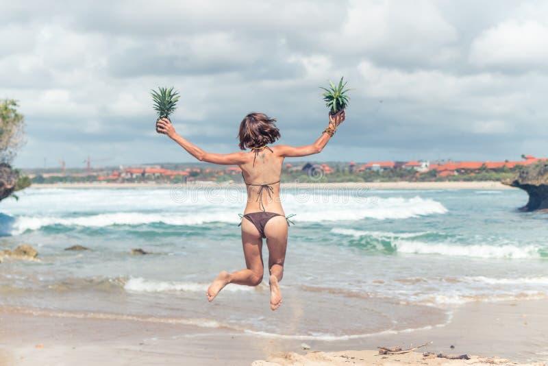Señora joven atractiva en el bikini que salta en la playa con la fruta sana cruda fresca de la piña Concepto feliz de las vacacio imagen de archivo