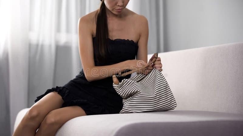 Señora joven atractiva en el vestido negro que desabrocha su bolso en el sofá, moda foto de archivo