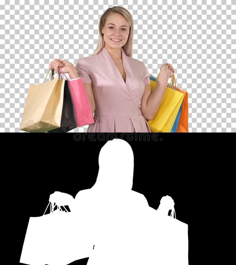 Señora joven bonita emocionada que se coloca de mirada de la cámara que muestra los bolsos de compras, Alpha Channel fotos de archivo
