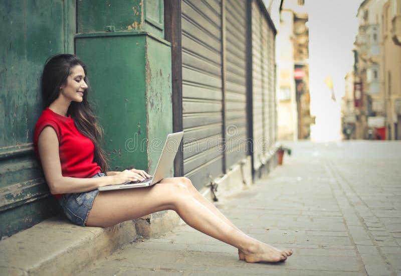 Señora joven con el ordenador portátil imagenes de archivo