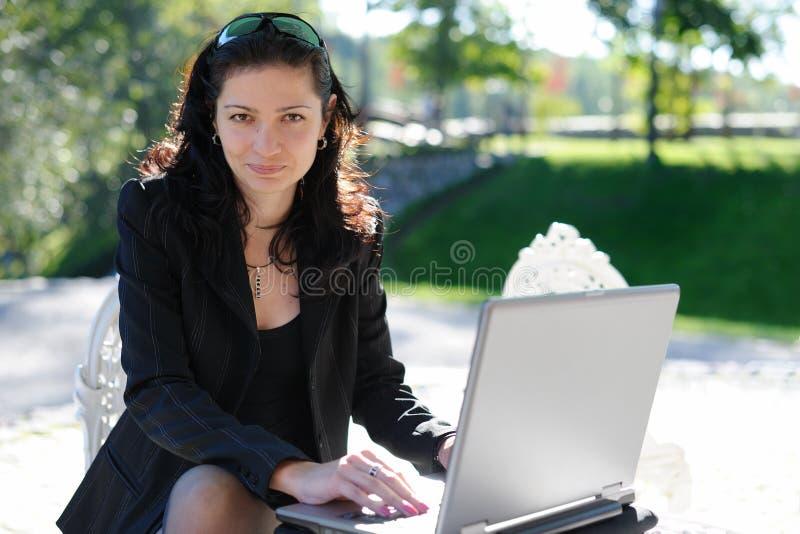 Señora joven con un cuaderno en un café del verano imagenes de archivo