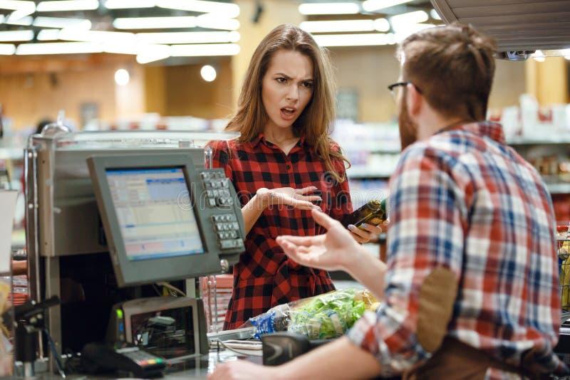 Señora joven confusa que se coloca en tienda del supermercado fotos de archivo