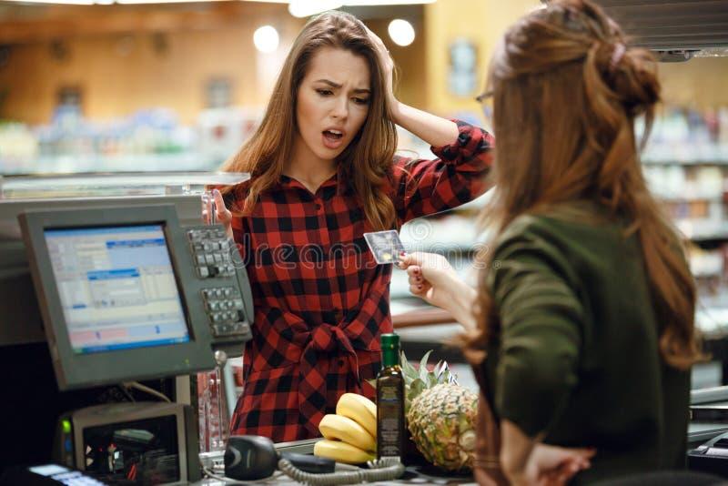Señora joven confusa que se coloca en tienda del supermercado cerca de cajero imagen de archivo