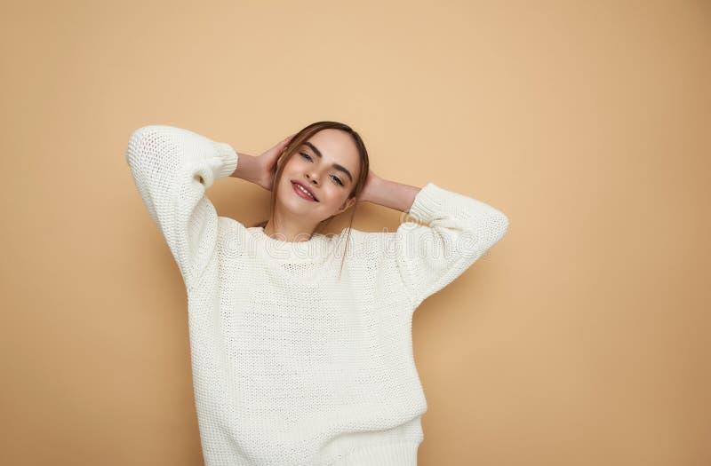 Se?ora joven contenta que pone las manos detr?s de su cabeza y sonrisa foto de archivo libre de regalías