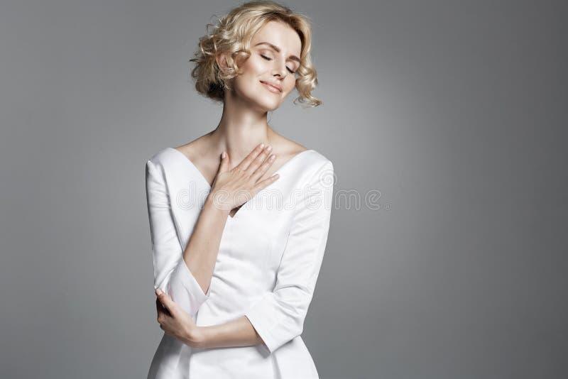 Señora joven del encanto que lleva el vestido blanco de moda imagen de archivo