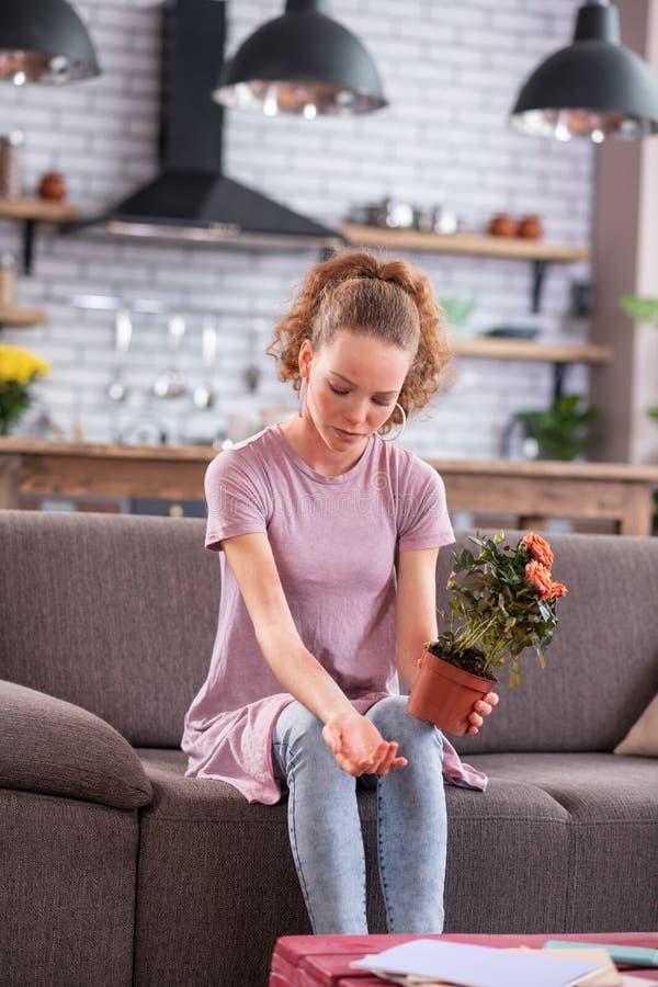 Señora joven del jengibre desgraciado que se sienta en el sofá gris con el pote fotografía de archivo libre de regalías