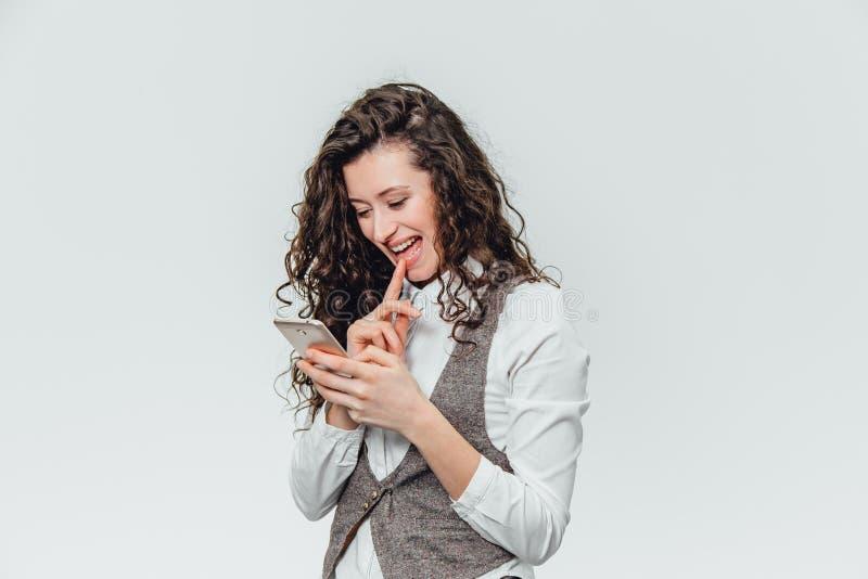 Señora joven del negocio con el pelo rizado hermoso en un fondo blanco Durante este tiempo, él ve emocionalmente sus fotos imagen de archivo libre de regalías