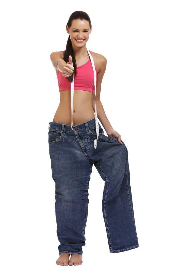 Señora joven delgada en los pantalones vaqueros grandes después de la dieta imagen de archivo