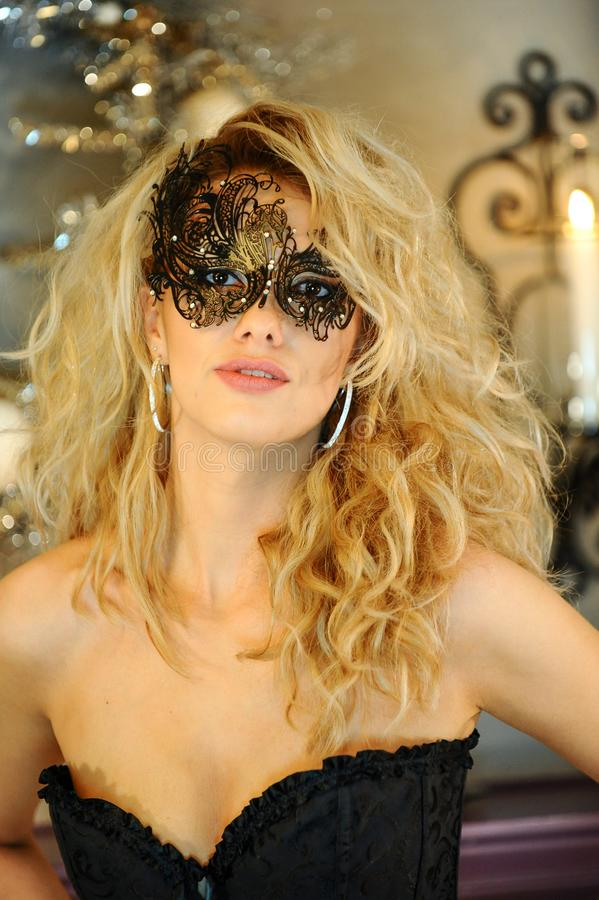 Señora joven elegante atractiva que lleva el corsé negro y la máscara veneciana foto de archivo