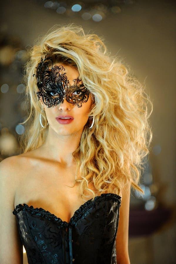 Señora joven elegante atractiva que lleva el corsé negro y la máscara veneciana fotografía de archivo