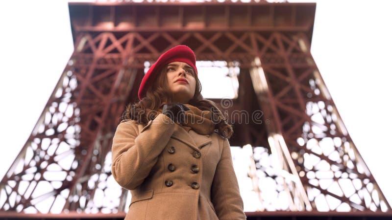 Señora joven en cuestión que coloca la torre Eiffel cercana sola, para amigo que espera fotos de archivo