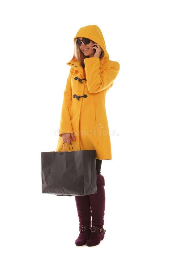 Señora joven en el teléfono mientras que hace compras fotos de archivo