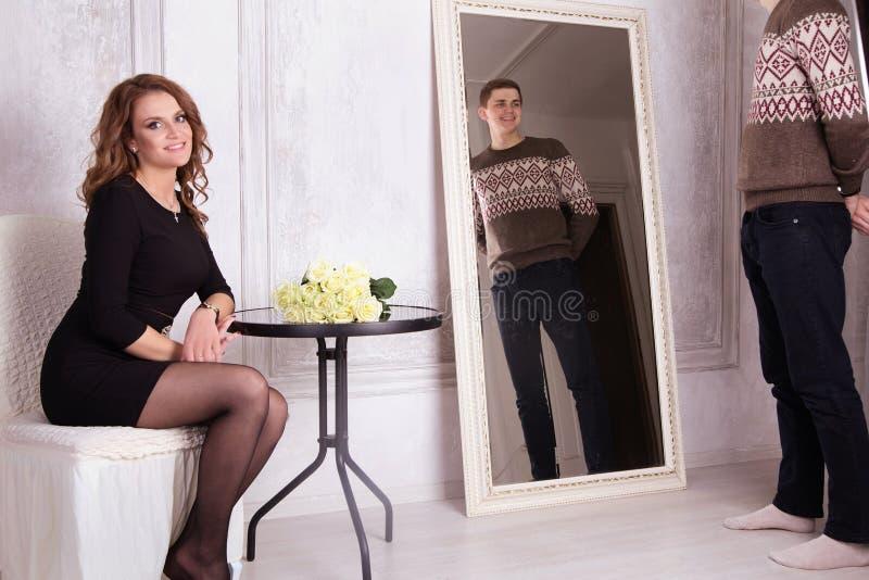 Señora joven en vestido negro y el hombre que miran el espejo fotos de archivo libres de regalías