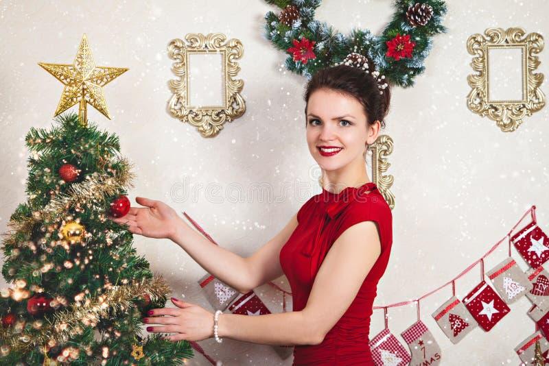 Señora joven en vestido rojo cerca del árbol de navidad fotografía de archivo