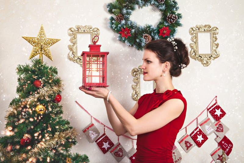 Señora joven en vestido rojo con la linterna de la Navidad imagen de archivo