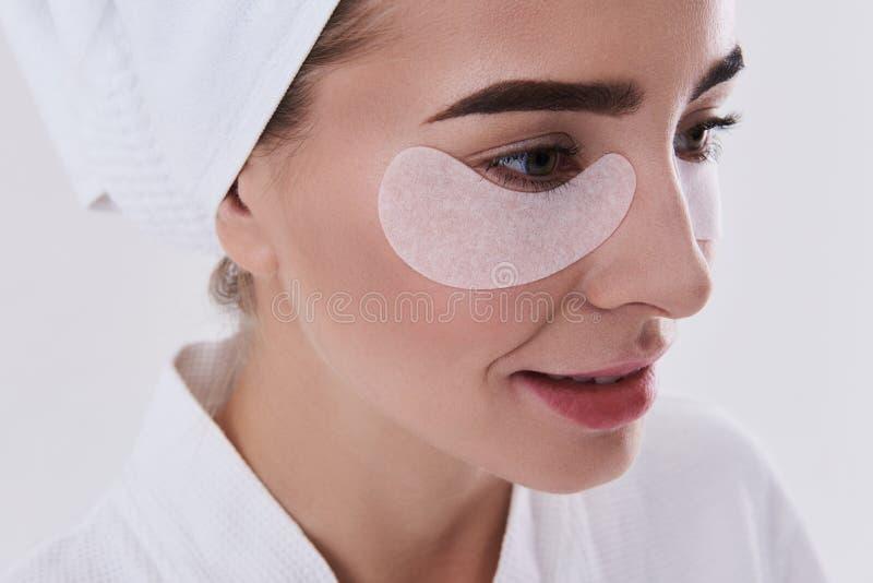 Señora joven encantadora con la toalla en la cabeza usando remiendos del debajo-ojo imágenes de archivo libres de regalías