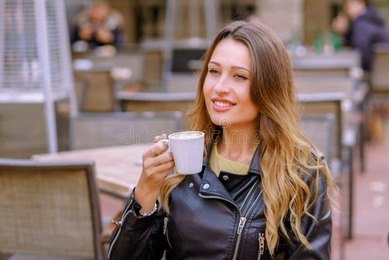 Señora joven encantadora que sonríe y que sostiene la taza de bebida caliente fresca mientras que se sienta en fondo borroso del  fotografía de archivo