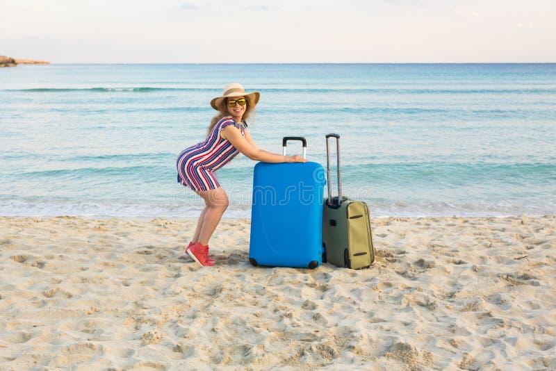 Señora joven hermosa con una maleta azul en la playa Concepto de la gente, del viaje, de las vacaciones y del verano imágenes de archivo libres de regalías