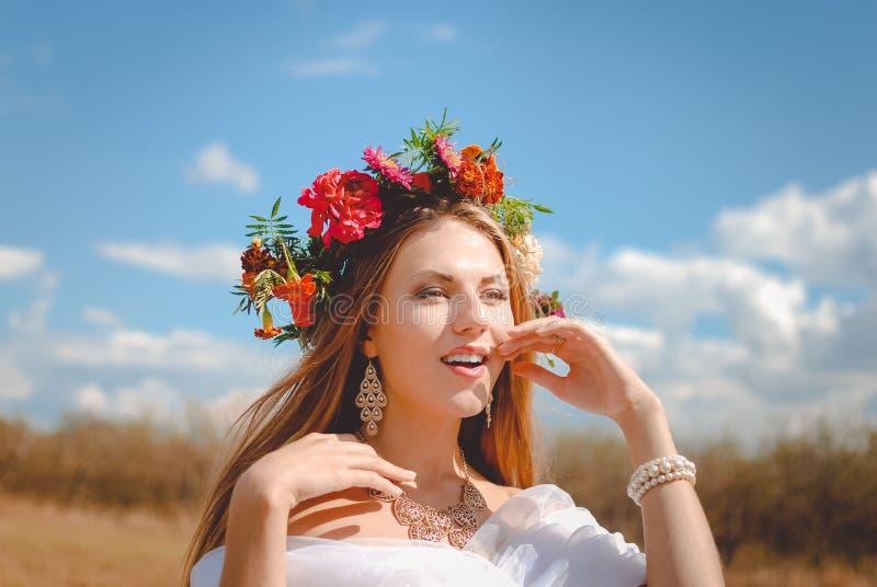 Señora joven hermosa en guirnalda de la maravilla y fotografía de archivo