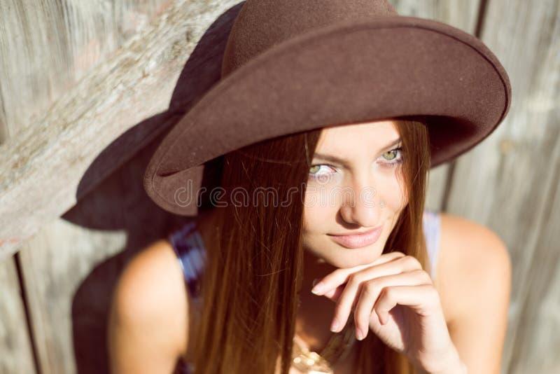 Señora joven hermosa en sombrero marrón que sonríe por otra parte fotografía de archivo libre de regalías