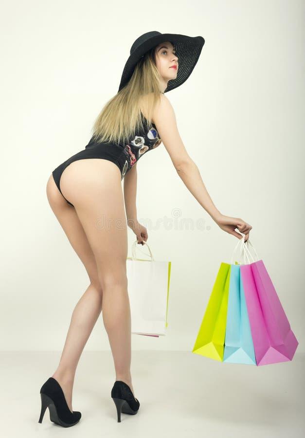 Señora joven hermosa en un bañador, sombrero negro grande en los tacones altos, sosteniendo bolsos coloridos La muchacha va a hac imagen de archivo libre de regalías