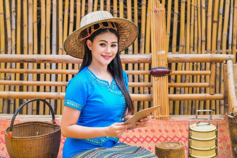 Señora joven hermosa en un vestido tailandés tradicional con la tableta para recibir pedidos del cliente fotografía de archivo libre de regalías