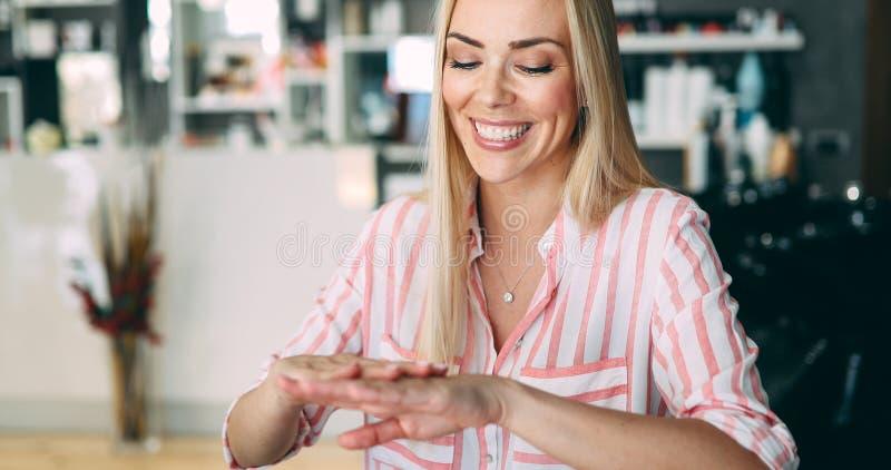 Señora joven hermosa que aplica la nata hidratante imágenes de archivo libres de regalías