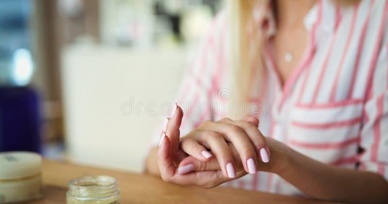 Señora joven hermosa que aplica la nata hidratante imagen de archivo