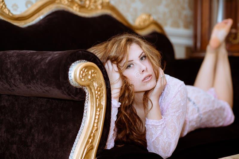 Señora joven hermosa que miente en el sofá de lujo adentro imagen de archivo